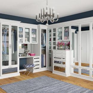 Réalisation d'un grand dressing room design pour une femme avec un placard à porte vitrée, des portes de placard blanches et un sol en bois clair.