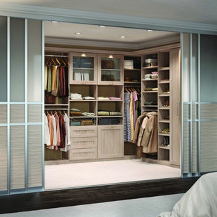 Large contemporary gender-neutral walk-in wardrobe in Los Angeles with shaker cabinets, carpet, light wood cabinets and beige floor.