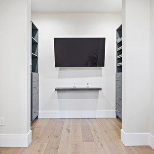 Ejemplo de armario vestidor unisex, minimalista, con armarios con paneles empotrados, puertas de armario azules, suelo de madera clara y suelo beige