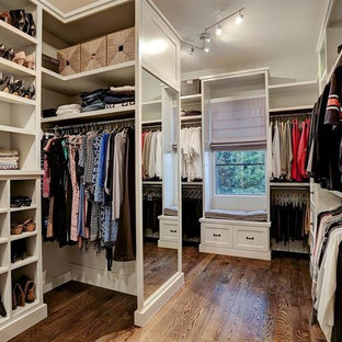 Inspiration for a large timeless gender-neutral brown floor and dark wood floor walk-in closet remodel in Houston with shaker cabinets and white cabinets