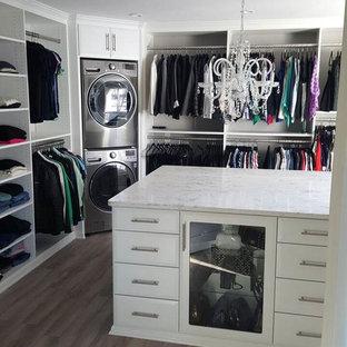 Ispirazione per uno spazio per vestirsi unisex moderno di medie dimensioni con ante con bugna sagomata, ante bianche e pavimento in legno massello medio