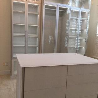 Foto de armario vestidor unisex, moderno, grande, con armarios tipo vitrina y suelo de piedra caliza