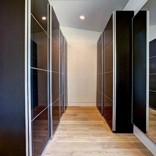 Idee per una cabina armadio unisex contemporanea di medie dimensioni con ante lisce, ante nere, parquet chiaro e pavimento beige