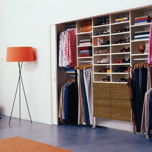 Inspiration for a modern gender-neutral built-in wardrobe in Los Angeles with flat-panel cabinets, white cabinets and concrete floors.