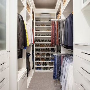 Medium sized classic gender neutral walk-in wardrobe in Dallas with flat-panel cabinets, white cabinets, carpet and brown floors.