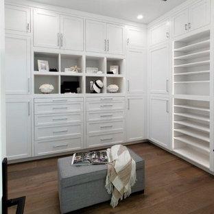 Imagen de vestidor de mujer, costero, grande, con armarios estilo shaker, puertas de armario blancas, suelo de madera oscura y suelo marrón