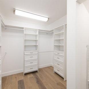 Imagen de armario y vestidor unisex, contemporáneo, de tamaño medio, con armarios con paneles con relieve, puertas de armario de madera oscura y suelo beige