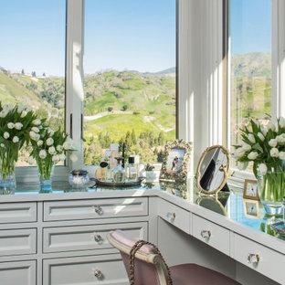 Mediterranes Ankleidezimmer mit Ankleidebereich, Schrankfronten mit vertiefter Füllung und grauen Schränken in Los Angeles