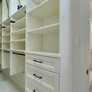 Immagine di una cabina armadio unisex tradizionale di medie dimensioni con ante con bugna sagomata, ante bianche, moquette e pavimento bianco