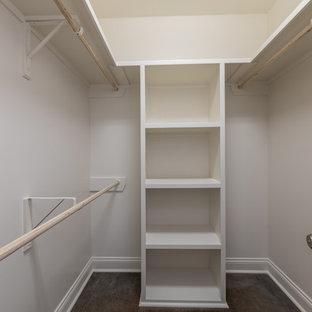 Ejemplo de armario vestidor unisex, campestre, de tamaño medio, con suelo de cemento y suelo marrón