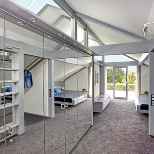 This is an example of a large contemporary gender neutral dressing room in Stuttgart with glass-front cabinets, carpet and grey floors.