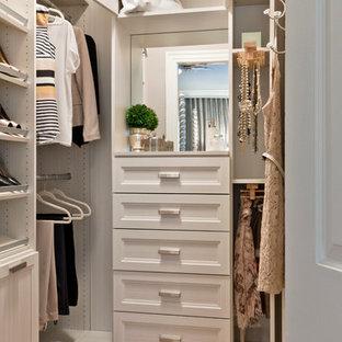 Réalisation d'un dressing tradition pour une femme avec un placard avec porte à panneau encastré, des portes de placard blanches et un sol en bois brun.
