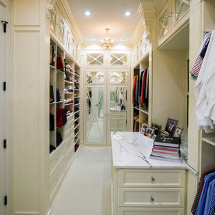 シャーロットの広い男女兼用トランジショナルスタイルのおしゃれなウォークインクローゼット (落し込みパネル扉のキャビネット、白いキャビネット、カーペット敷き、白い床) の写真