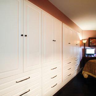 Imagen de armario de mujer, tradicional, de tamaño medio, con armarios con paneles con relieve, puertas de armario blancas y suelo de madera oscura