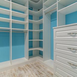 Cette image montre un dressing traditionnel de taille moyenne et neutre avec un placard avec porte à panneau surélevé, des portes de placard blanches et un sol en vinyl.
