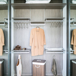 Diseño de armario unisex, industrial, de tamaño medio, con armarios con paneles lisos, puertas de armario grises, suelo de madera en tonos medios y suelo gris