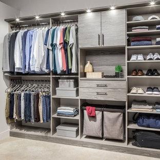 Imagen de armario vestidor de hombre, contemporáneo, grande, con armarios abiertos, puertas de armario grises, suelo de madera clara y suelo beige