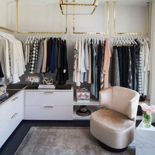 Imagen de armario vestidor de mujer, actual, de tamaño medio, con armarios con paneles lisos, puertas de armario blancas, suelo de madera oscura y suelo negro