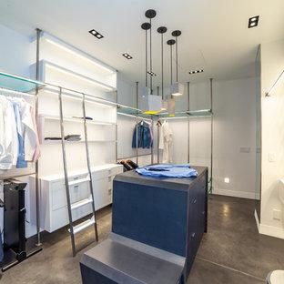 Imagen de vestidor unisex, minimalista, extra grande, con armarios con paneles lisos, puertas de armario azules, suelo de cemento y suelo gris