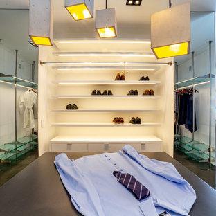 Ejemplo de vestidor unisex, moderno, extra grande, con armarios con paneles lisos, puertas de armario azules, suelo de cemento y suelo gris