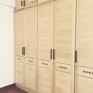Esempio di armadi e cabine armadio eclettici di medie dimensioni con ante con riquadro incassato e ante in legno chiaro