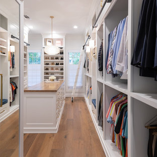 This is an example of a country gender-neutral dressing room in Houston with open cabinets, white cabinets, medium hardwood floors and brown floor.