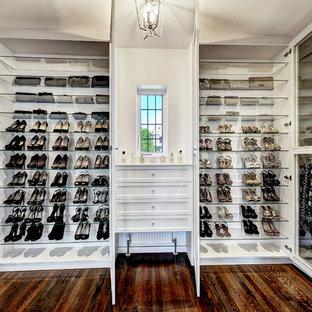 Diseño de armario vestidor de mujer, vintage, grande, con armarios tipo vitrina, puertas de armario blancas y suelo de madera oscura