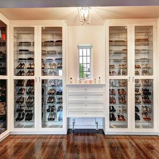 Ejemplo de armario vestidor de mujer, tradicional renovado, grande, con armarios tipo vitrina, puertas de armario blancas y suelo de madera oscura