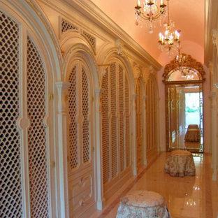 Esempio di uno spazio per vestirsi per donna mediterraneo con ante con bugna sagomata, ante in legno chiaro e pavimento in marmo
