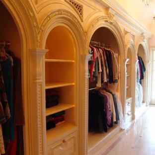 Idee per uno spazio per vestirsi per donna mediterraneo con ante con bugna sagomata, ante in legno chiaro e pavimento in marmo