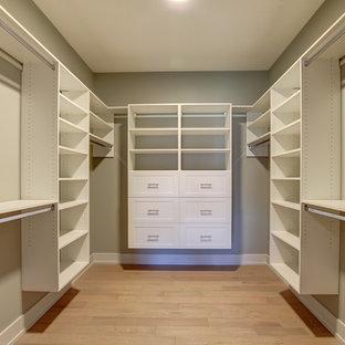 Idee per una cabina armadio unisex design di medie dimensioni con ante in stile shaker, ante bianche, parquet chiaro e pavimento marrone
