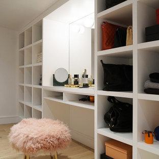 Ejemplo de vestidor de mujer, contemporáneo, de tamaño medio, con armarios abiertos, puertas de armario blancas, suelo de madera clara y suelo marrón