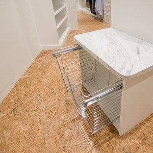 Foto di una cabina armadio unisex industriale con nessun'anta, ante bianche, pavimento in sughero e pavimento beige