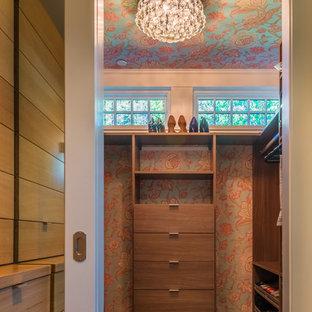 Imagen de armario vestidor de mujer, bohemio, de tamaño medio, con armarios con paneles lisos, puertas de armario de madera oscura y suelo de madera oscura