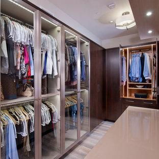 Diseño de vestidor unisex, contemporáneo, pequeño, con armarios tipo vitrina, puertas de armario de madera en tonos medios, suelo de madera clara y suelo gris