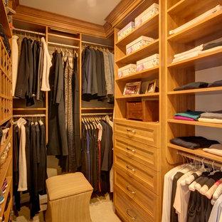 Modelo de armario vestidor unisex, tradicional, de tamaño medio, con armarios abiertos, puertas de armario de madera clara, moqueta y suelo beige
