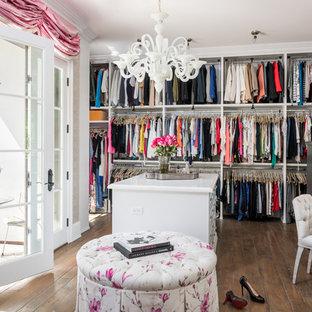 Imagen de armario vestidor de mujer, mediterráneo, con armarios abiertos, puertas de armario blancas, suelo de madera oscura y suelo marrón