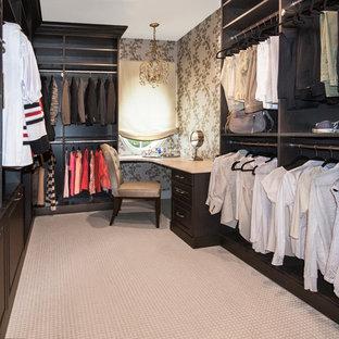 Inredning av ett klassiskt stort walk-in-closet för kvinnor, med luckor med upphöjd panel, skåp i mellenmörkt trä och heltäckningsmatta