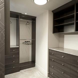 Imagen de armario vestidor unisex, tradicional, grande, con armarios con paneles lisos, puertas de armario de madera oscura y suelo de travertino