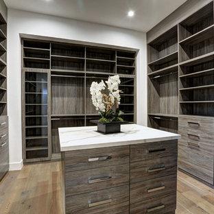 Immagine di una grande cabina armadio unisex minimalista con ante lisce, ante in legno chiaro, parquet chiaro e pavimento marrone