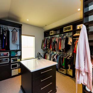 Immagine di un grande spazio per vestirsi unisex stile marino con ante lisce, ante in legno bruno e moquette