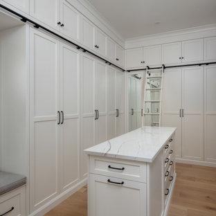 Ejemplo de armario vestidor unisex, tradicional renovado, extra grande, con armarios estilo shaker, puertas de armario blancas, suelo de madera clara y suelo beige