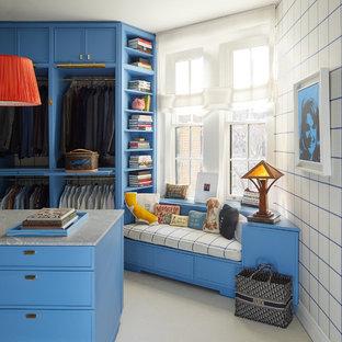 Cette photo montre un dressing room tendance pour un homme avec moquette, des portes de placard bleues et un sol gris.