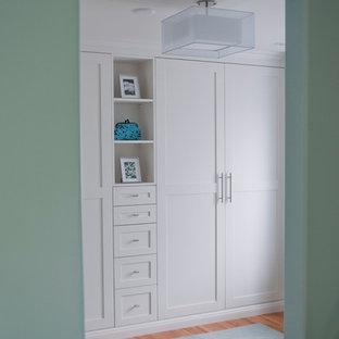 Imagen de armario y vestidor clásico renovado con armarios estilo shaker, puertas de armario blancas y suelo de madera clara