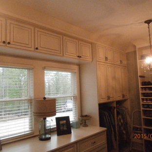 Mid-sized traditional women's dressing room in Atlanta with raised-panel cabinets, distressed cabinets and light hardwood floors.