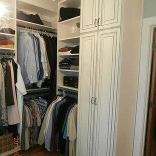 Imagen de vestidor de hombre, tradicional, de tamaño medio, con armarios con paneles con relieve, puertas de armario con efecto envejecido y suelo de madera clara
