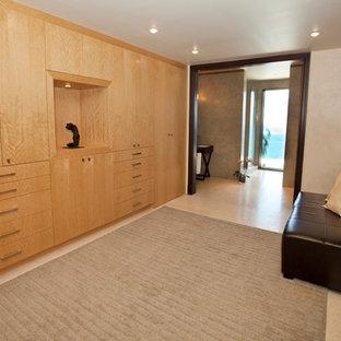 Ejemplo de vestidor tropical, grande, con armarios con paneles lisos y puertas de armario de madera clara