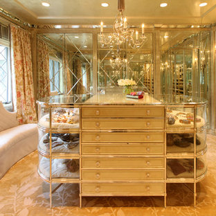 Inspiration for an expansive traditional women's walk-in wardrobe in New York with glass-front cabinets and carpet.