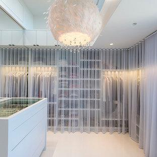 Idée de décoration pour un armoire et dressing design pour une femme avec un placard sans porte et des portes de placard blanches.