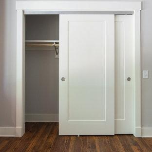 Ejemplo de armario unisex, tradicional, de tamaño medio, con suelo laminado y suelo marrón